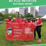 2019 Bike Ambassadors holding sign advertising free helmet fittings.