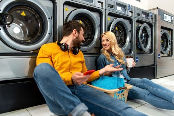 Young-cheerful-couple-doing-laundry-together-at-laundromat-shop-talking-cm