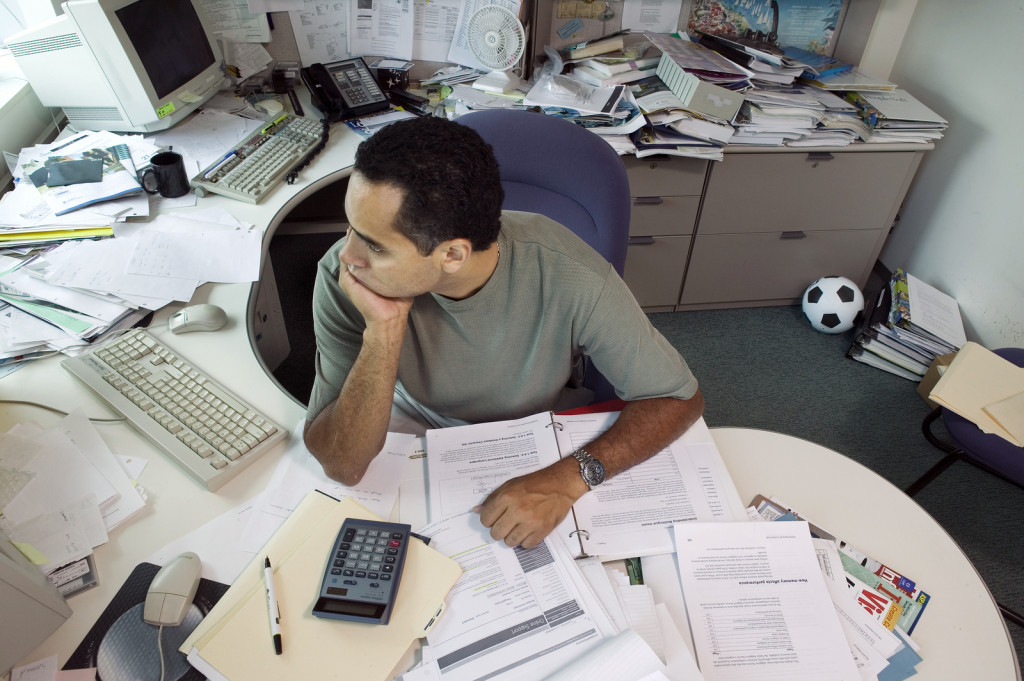 bigstock-Businessman-sitting-at-messy-d-29849984