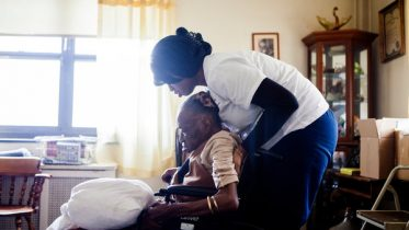Alicia Joseph, a home health aide with Partners in Care, helps Naomi Wallace, a dementia patient.