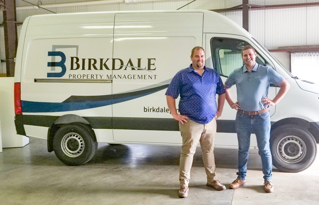 Jon and Brandon Israels posed in front of Birkdale Property Management's service van.