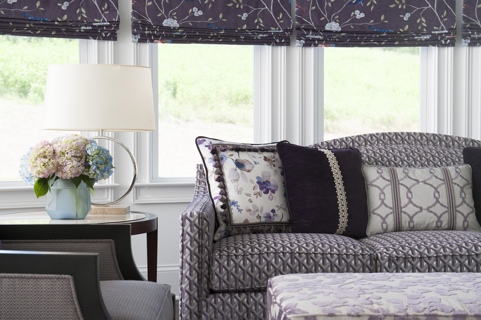 Roman shades raised in a bold, purple-inspired living room