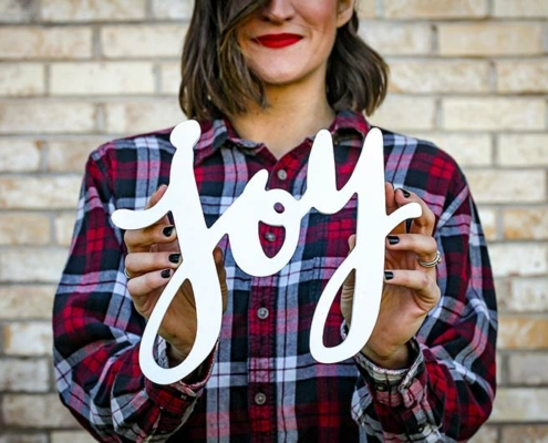 woman holding 'joy' sign