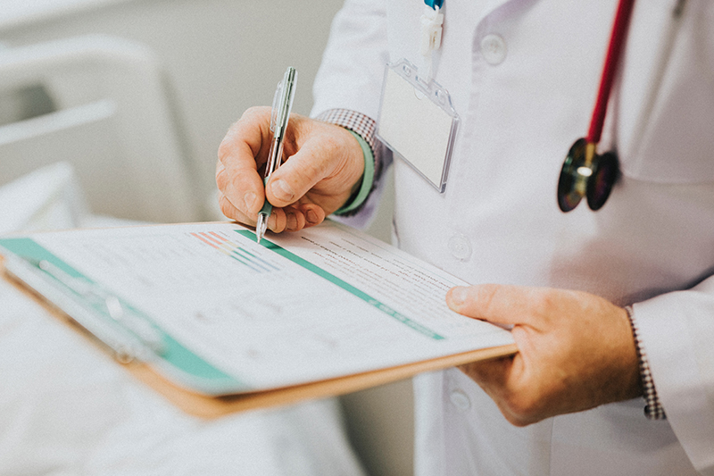 Doctor reading printed-out protected health information (PHI) on a clipboard