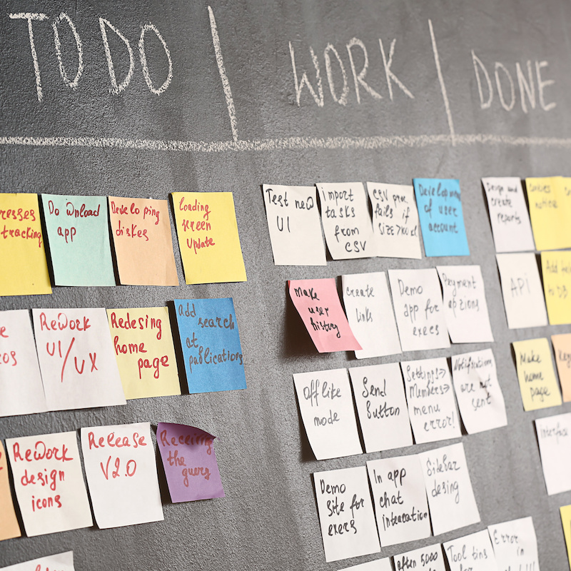Blackboard with sticky notes depicting project management for healthcare