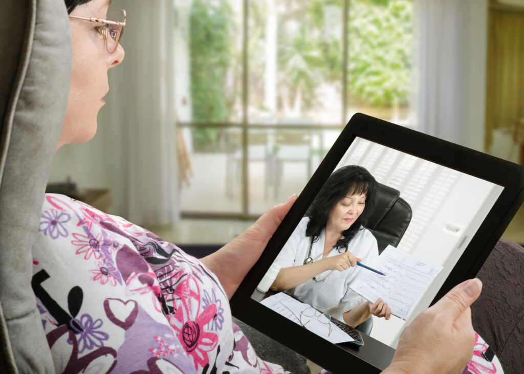 Woman-in-floral-shirt-watching-an-iPad-of-her-doctor-giving-her-health-counseling-as-an-example-of-telemedicine-in-rural-areas