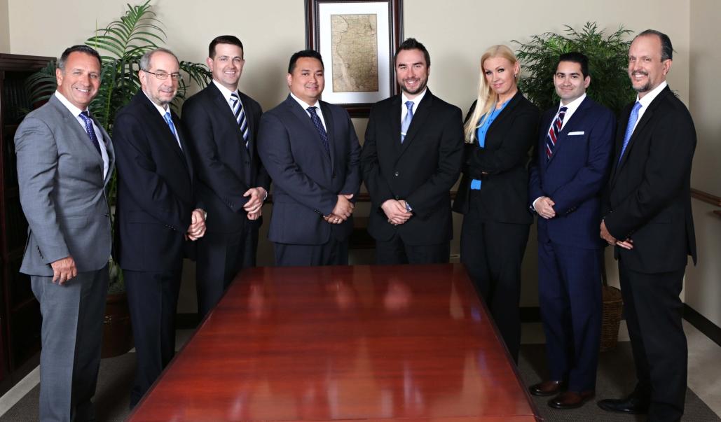 Woodruff Johnson & Evans Attorneys stand around a table