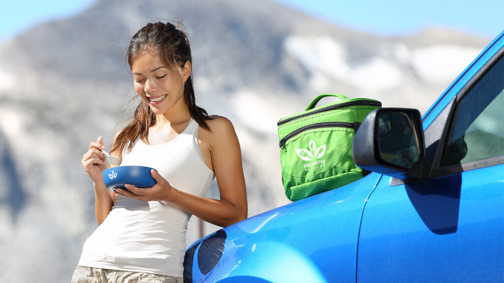 A woman stands in front of her car eating with a custom branded bowl and utensil kit. Behind her, a custom branded cooler sits on the hood of her car.