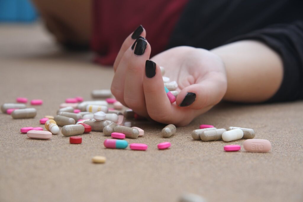woman's open hand holding various opioid capsules and pills
