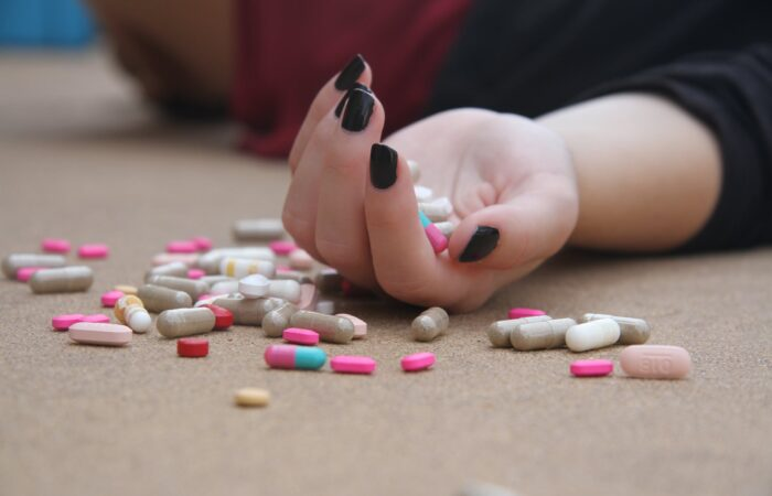 woman's open hand holding opioid capsules and pills