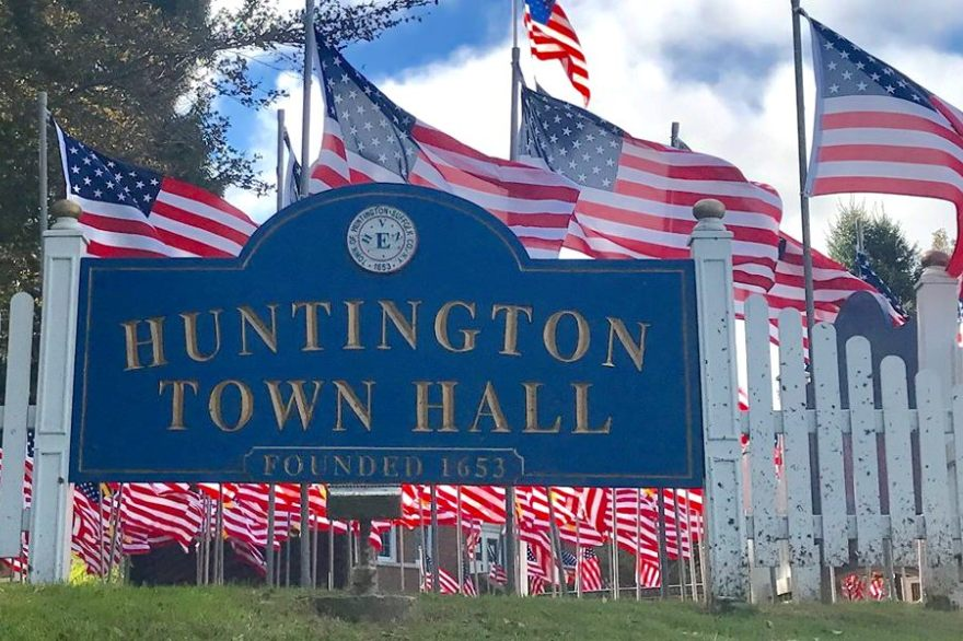 Huntington NY Town Hall sign with American Flags in the background