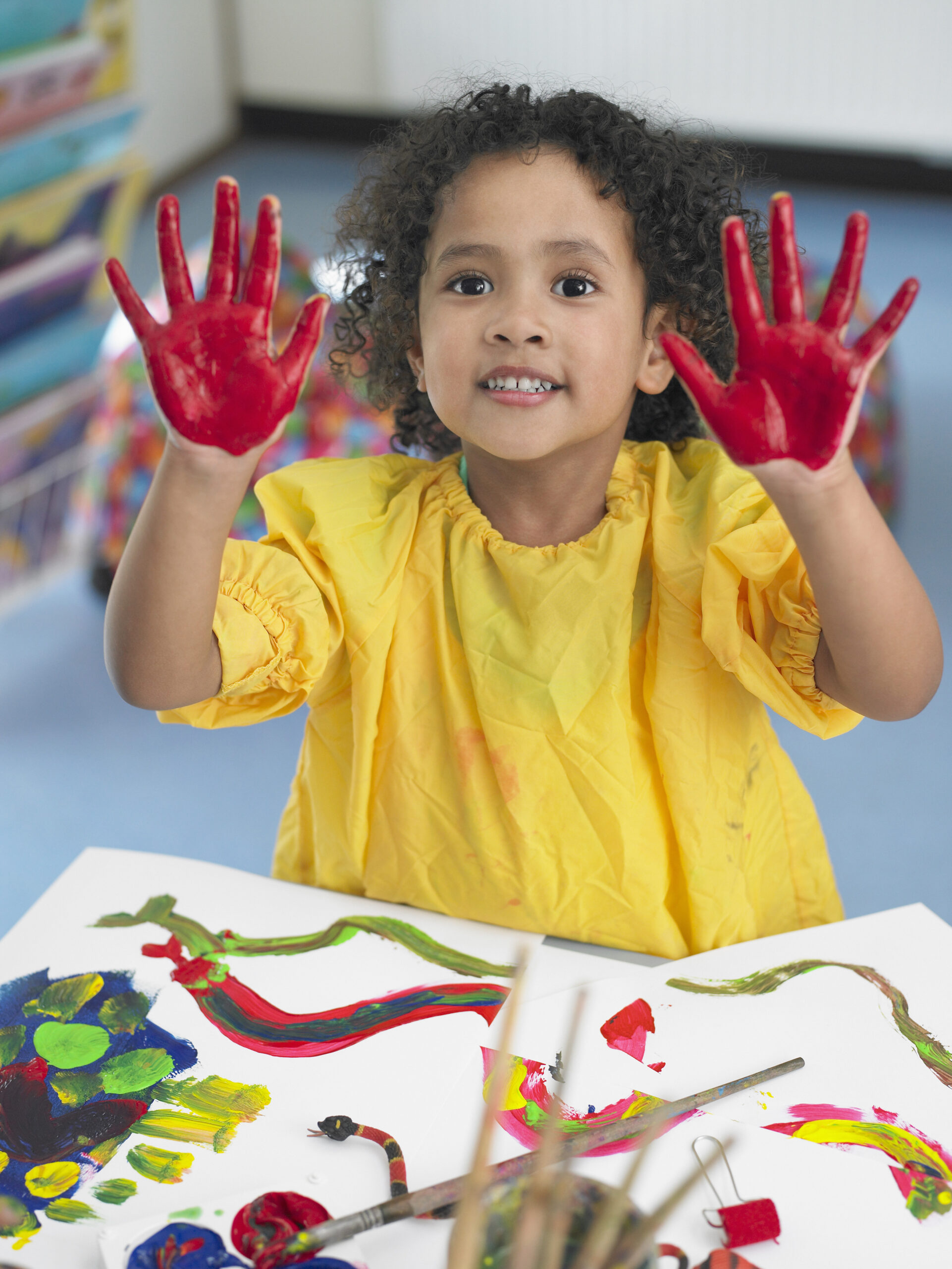 Portrait of cute little girl finger painting in art class
