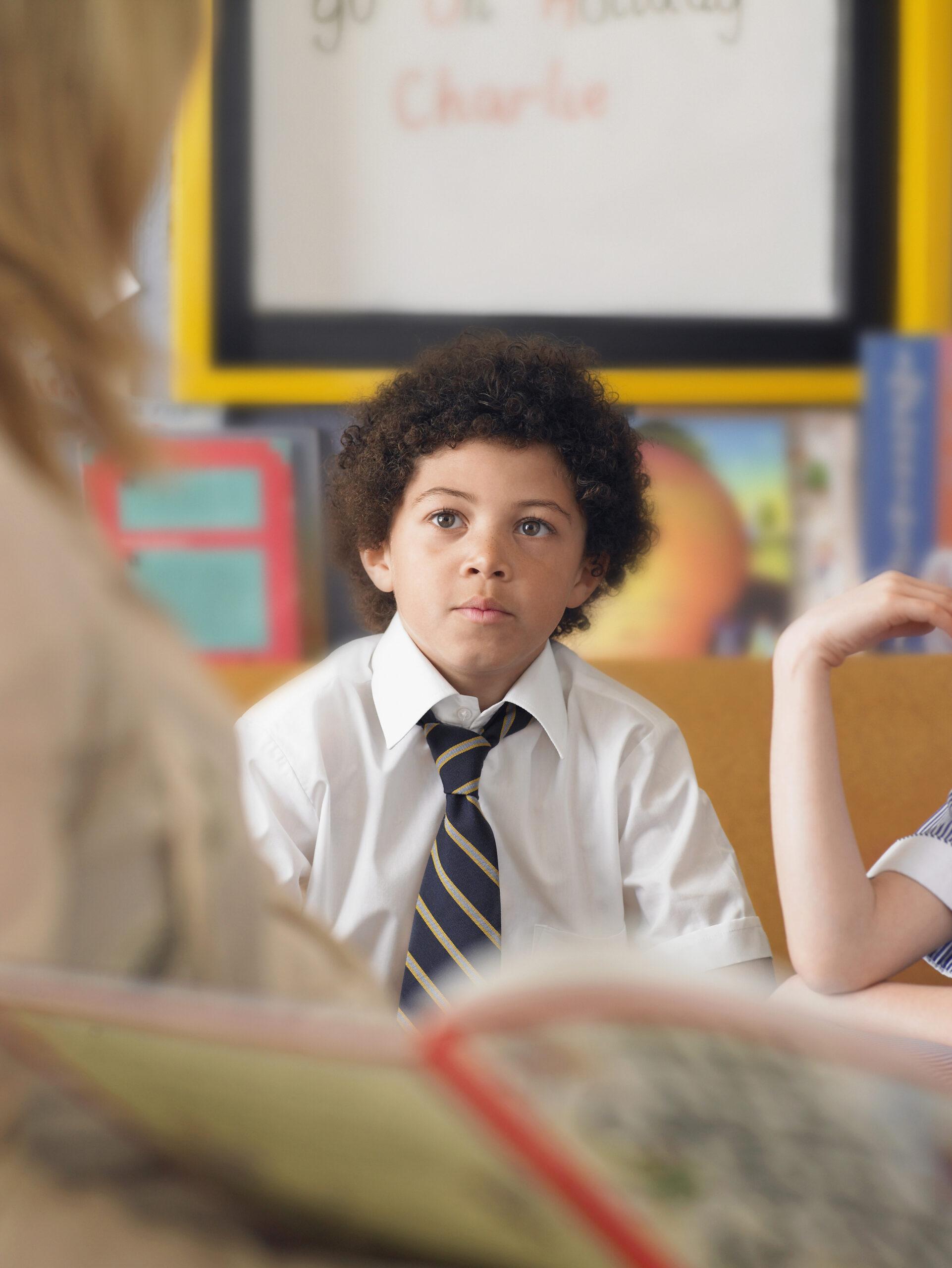 Elementary schoolboy listening to teacher reading in classroom