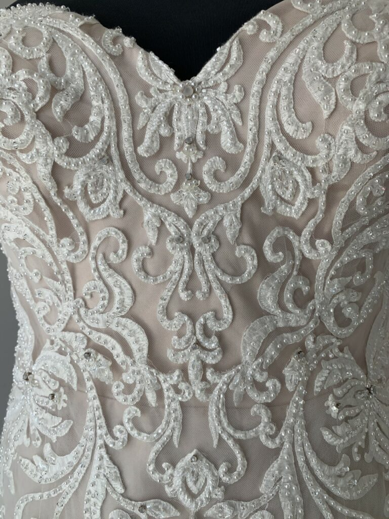 close up of lace wedding dress with pearls