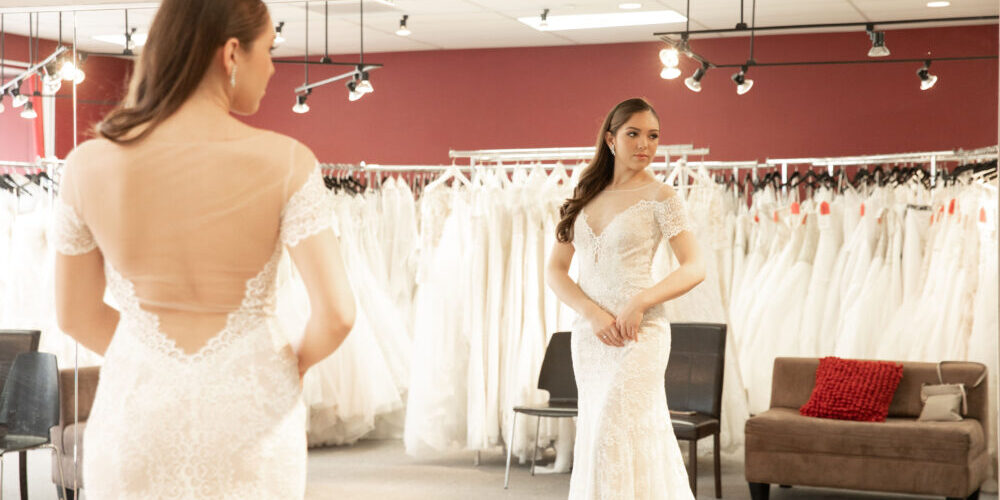 bride in off the shoulder sleeve lace wedding dress in bridal shop with rack of wedding gowns behind her whittier california