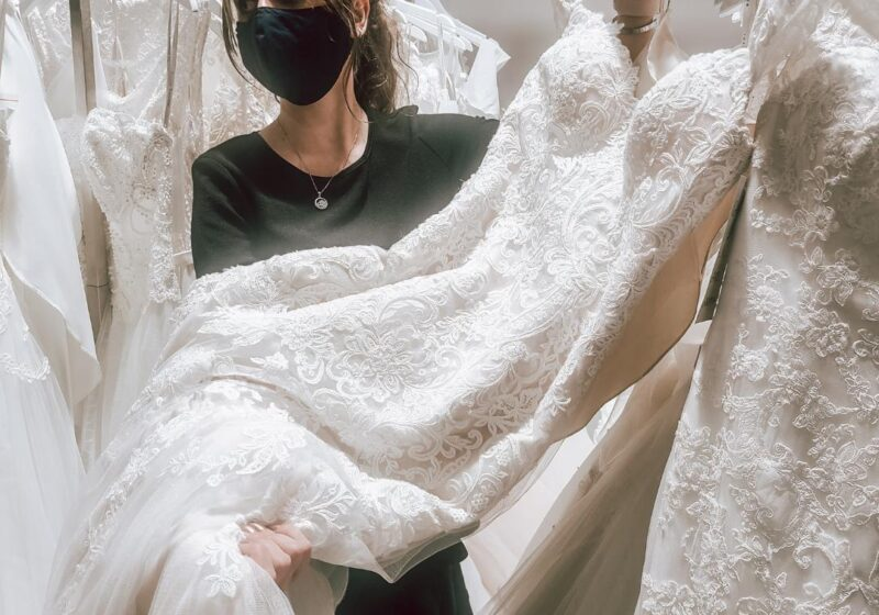 lace wedding dress on display with bridal stylist wearing mask