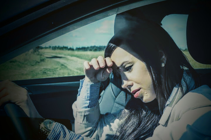 woman in car with hands on steering wheel looking upset