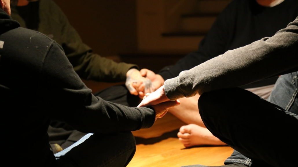 Holding hands at addiction recovery group in Portland