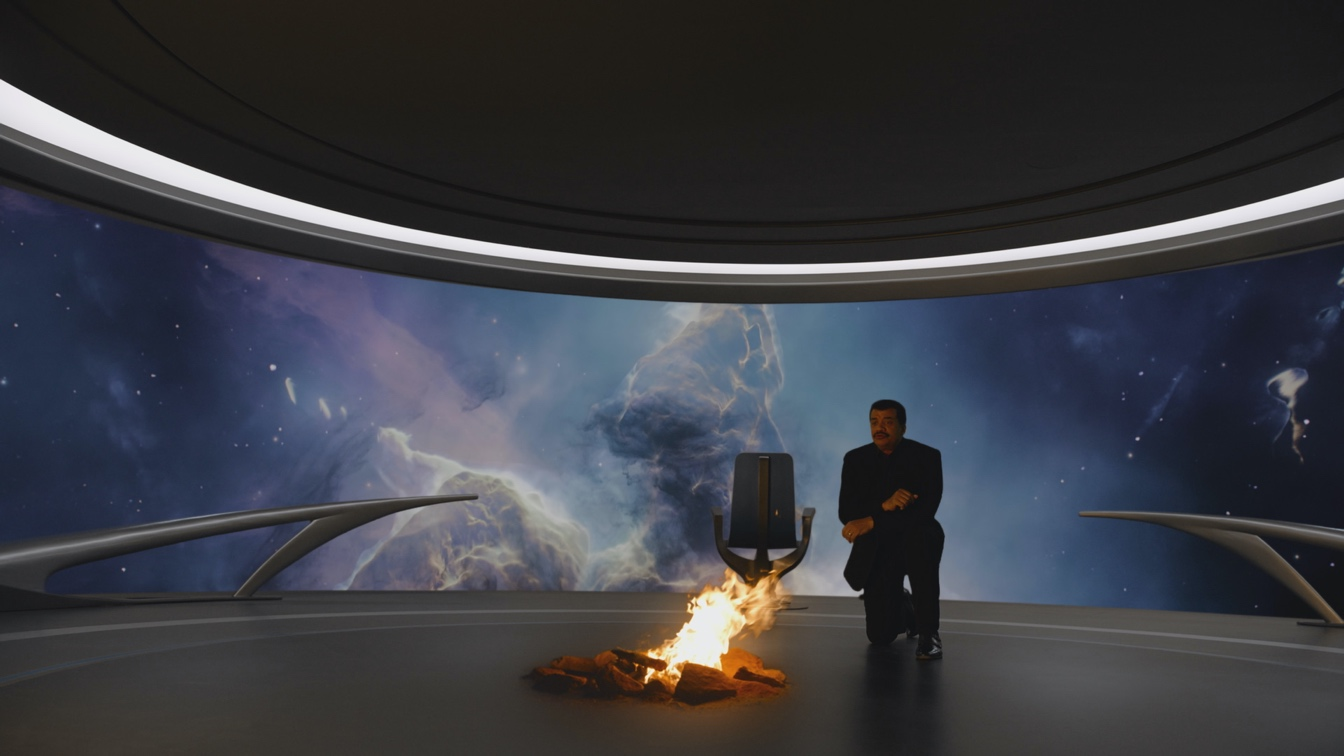 Host Neil deGrasse Tyson kneels before a fire on the Ship of the Imagination. Much as our ancestors used fire without understanding how it worked, we  have lived with the mystery of quantum physics for decades, while finding ways to exploit it. COSMOS: POSSIBLE WORLDS premieres March 9, 2020 on National Geographic. (Cosmos Studios)