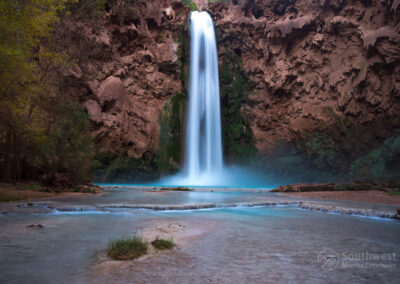 A view of Mooney Falls with a little island in the middle of the creek.