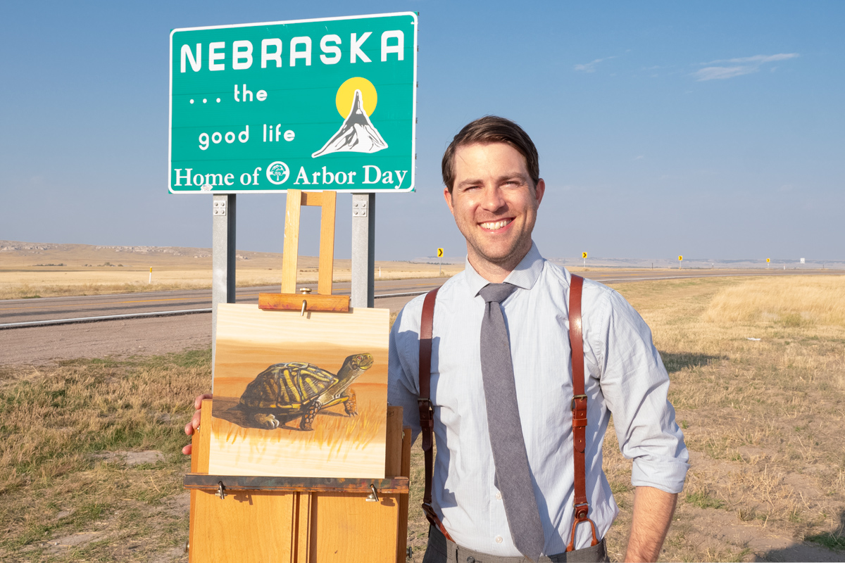 Artist Timothy Tim Davison with Nebraska state sign on highway with painting of western box turtle