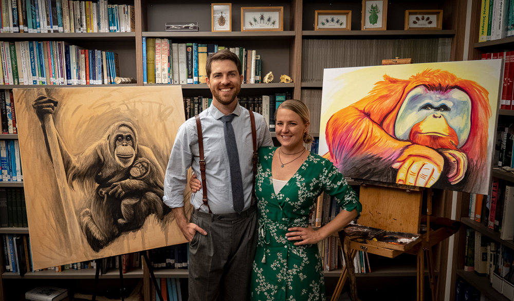 Timothy Davison and Stephanie Arne posing with paintings at a fundraising auction event