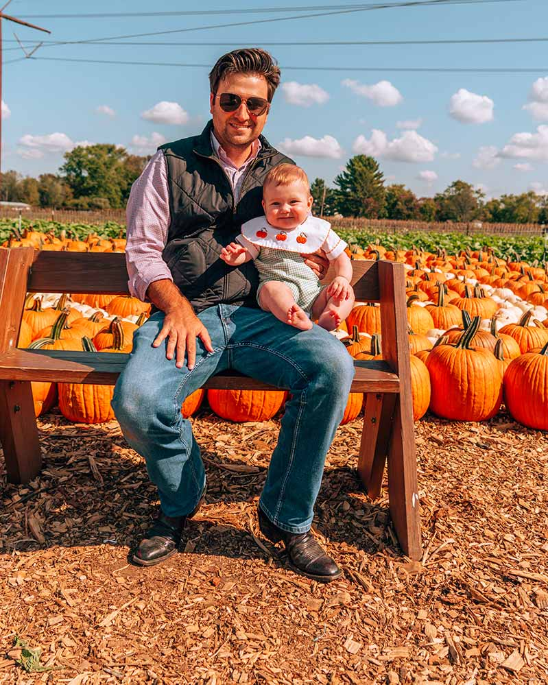 Man and Baby sitting on bench in front of pumpkin patch