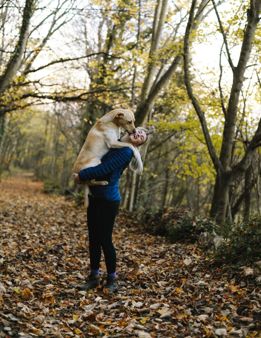 woman-carrying-dog-while-standing-in-the-middle-of-the-1612861