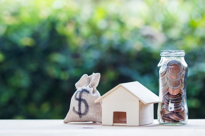 US-dollar-in-a-money-bag,-small-residential,-house-model-on-table-against-green-nature-background-cm