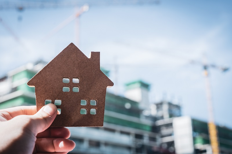 """House model in home insurance broker agent """"u2018s hand or in salesman person. Real estate agent offer house, property insurance and security, affordable housing concepts"""