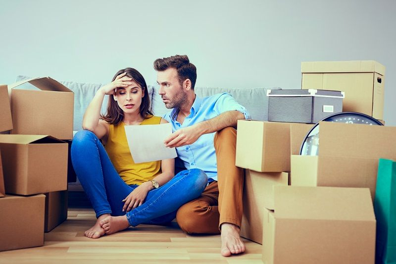 Worried-couple-reading-agreement-after-moving-to-new-home-cm