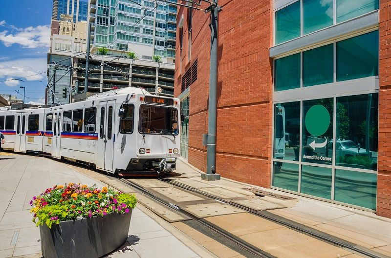 Light-rail-train-traveling-through-a-sun-filled-city-cm