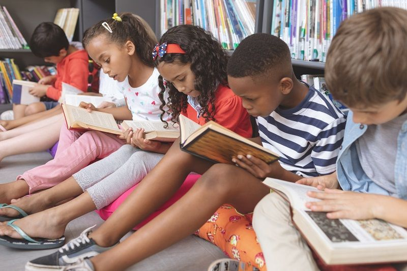 School-kids-sitting-on-cushions-and-studying-over-books-in-a-library-cm