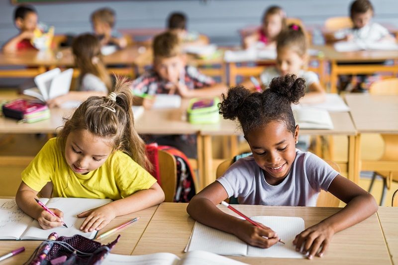 Happy-schoolgirls-writing-a-dictation-on-a-class-at-school.-cm