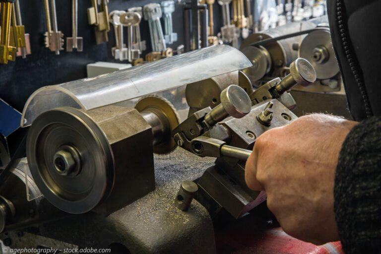 Locksmith cutting key on key cutting machine