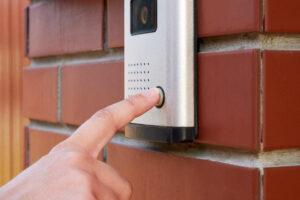 Finger activating a residential video intercom doorbell