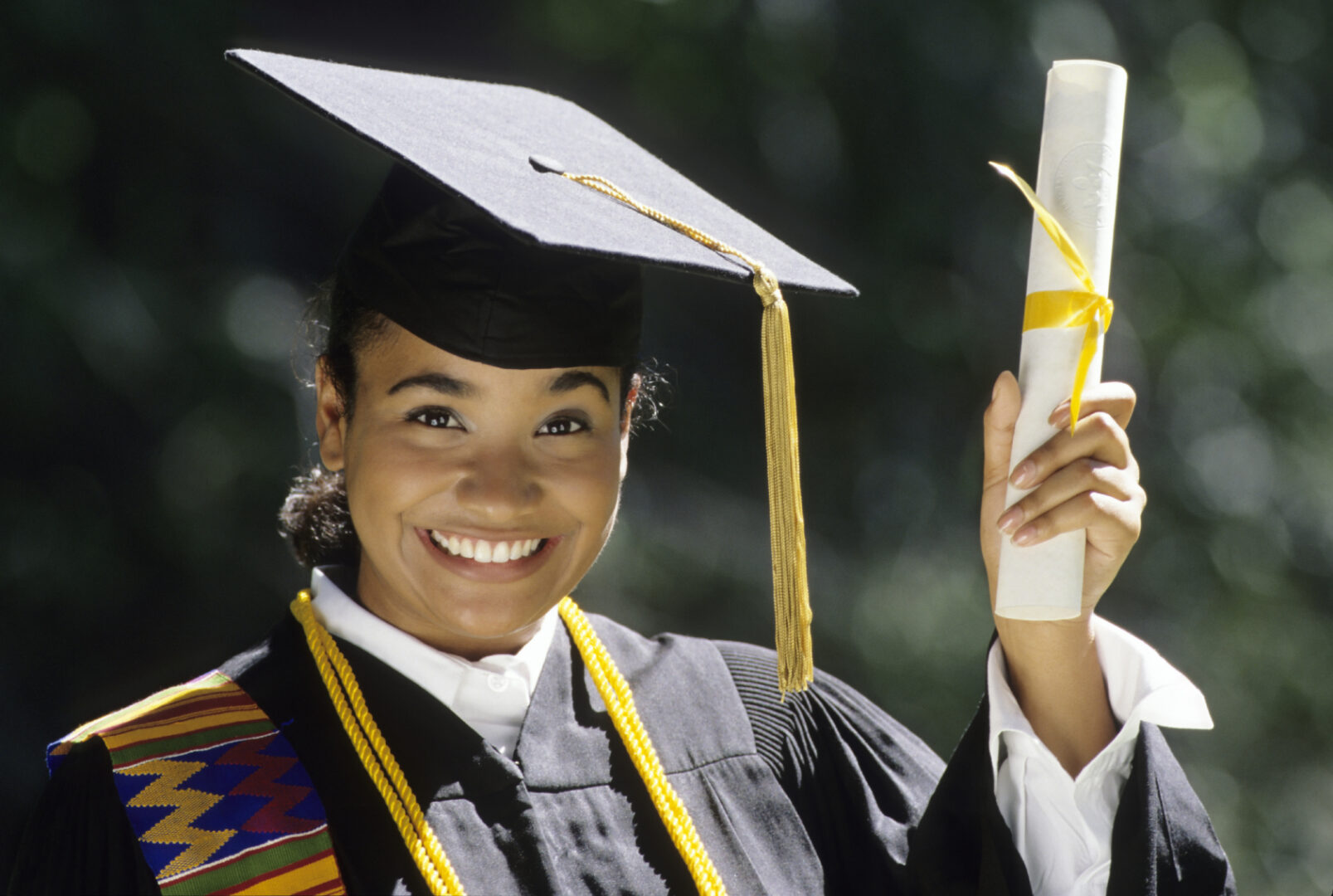 African American woman graduate wearing cap and gown holding up diploma