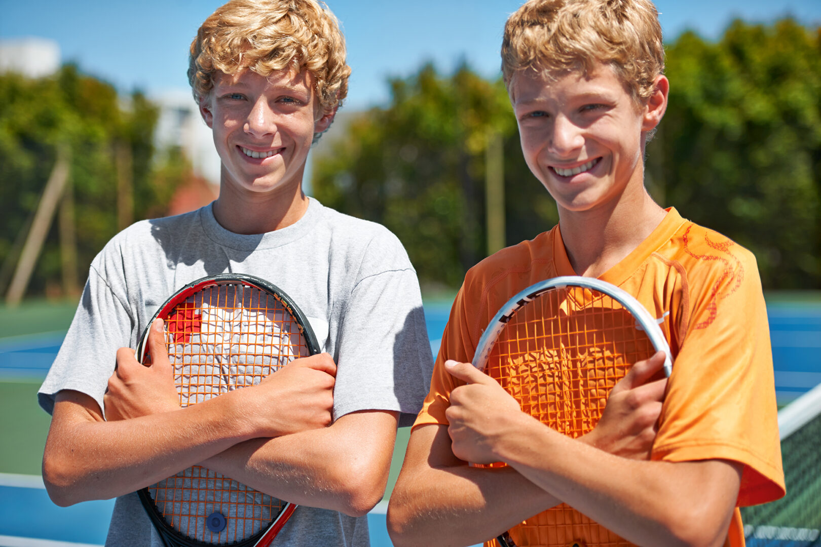 Two friends standing together and holding their tennis rackets on the court