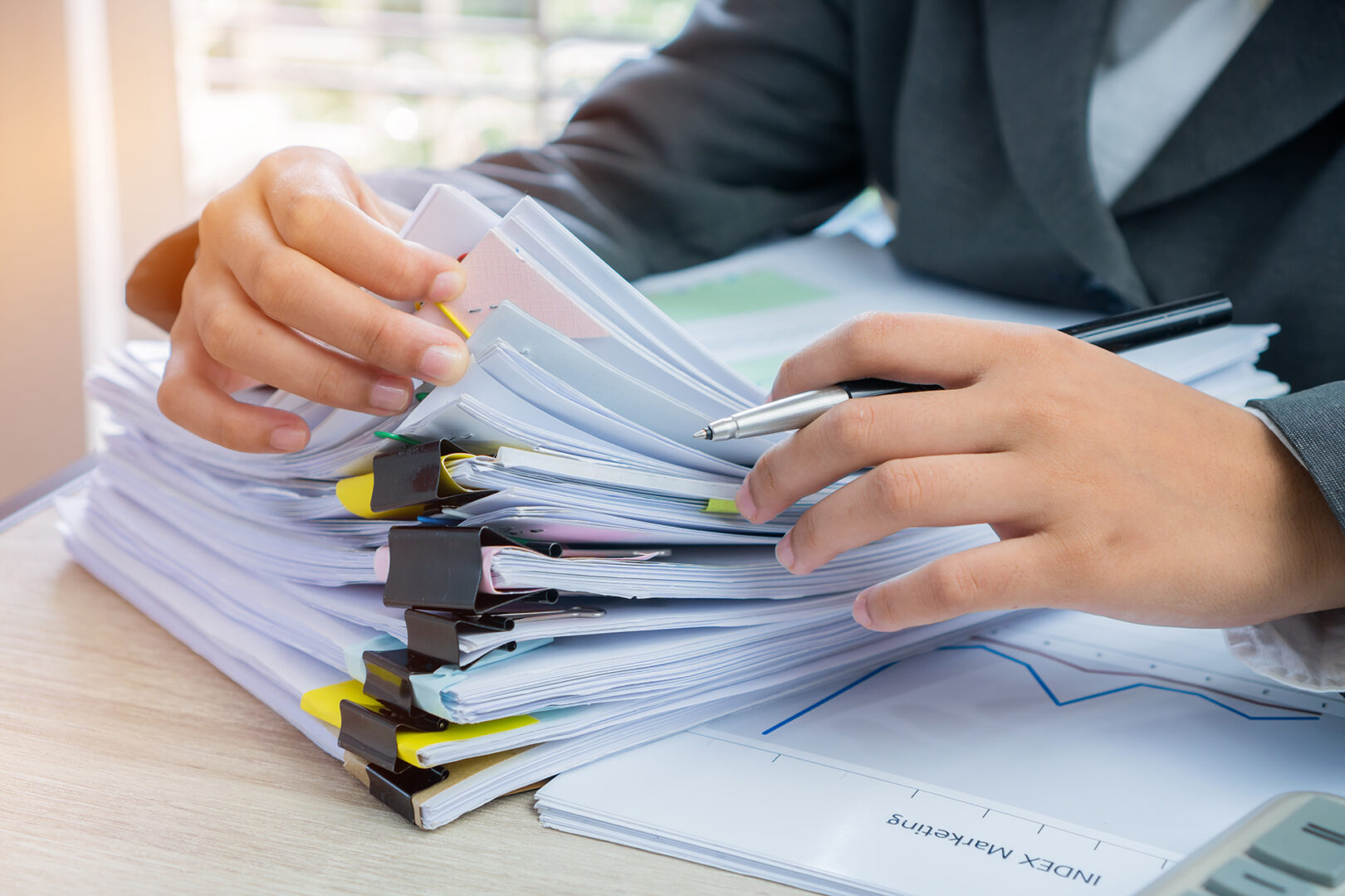 Hands young female business managers checking and arranging stack of unfinished documents reports papers for result graph marketing, startup project for plan job succes in Busy office with flare light