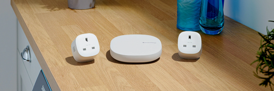 Samsung SmartThings Hub and Two SmartThings plugs resting on table
