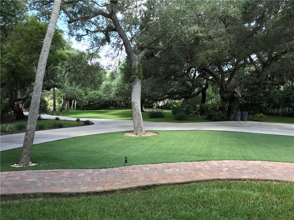 The beautiful grounds include a circular driveway and walkways adorned by majestic trees.