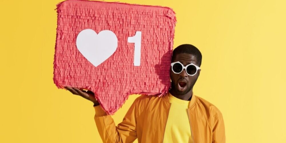 A social media influencer holds up a love emoji sign.