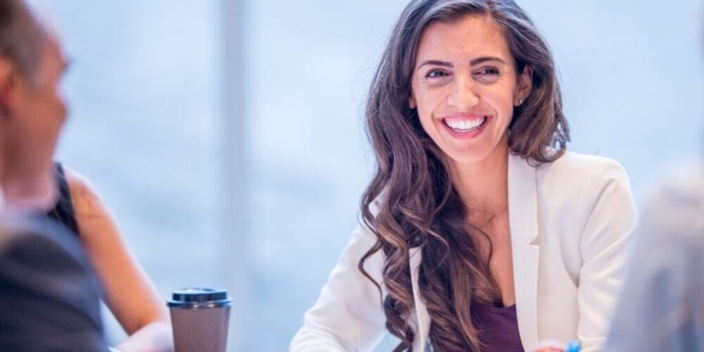 A smiling business professional at a meeting.