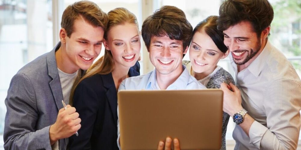 A group of company employees cheer at the new website.