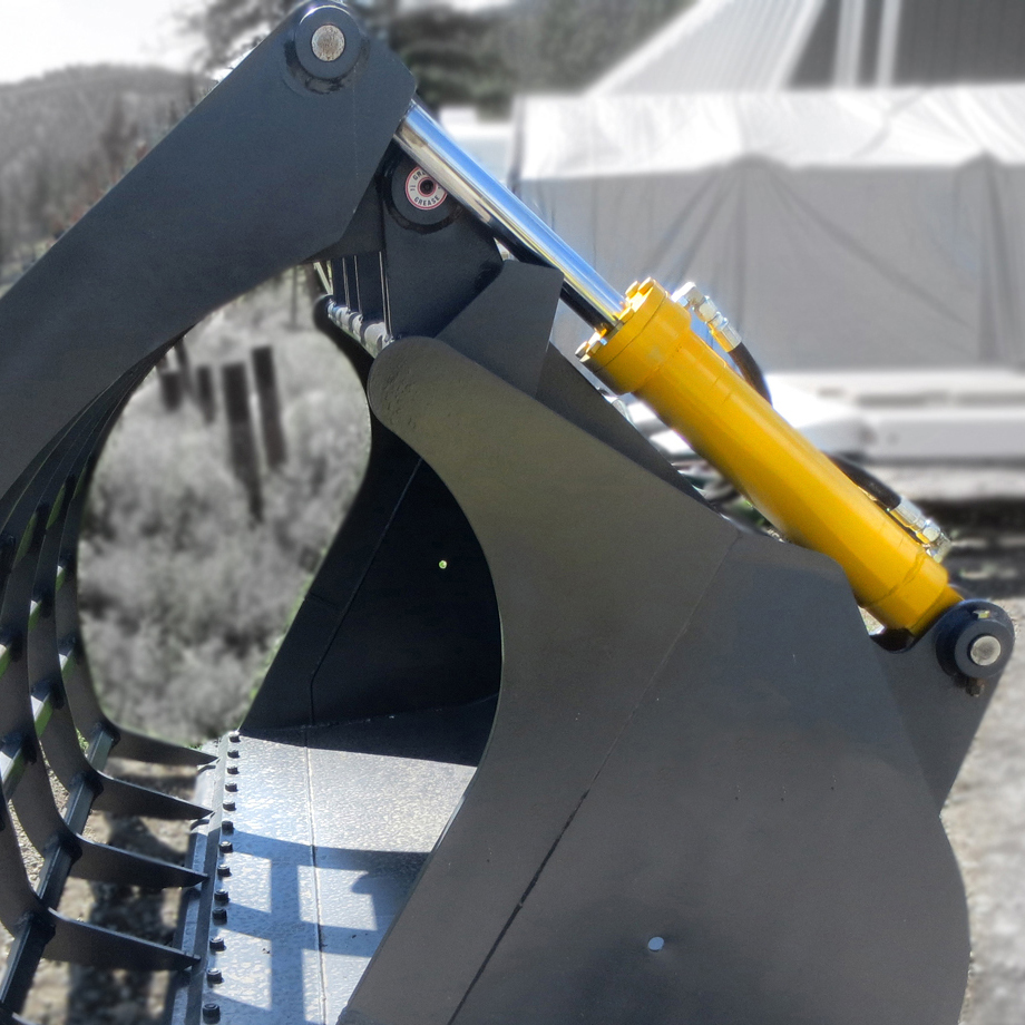 Heavy duty dual wheel loader hydraulic cylinders installed onto a wheel loader corral bucket, used in feedlot and agricultural applications.