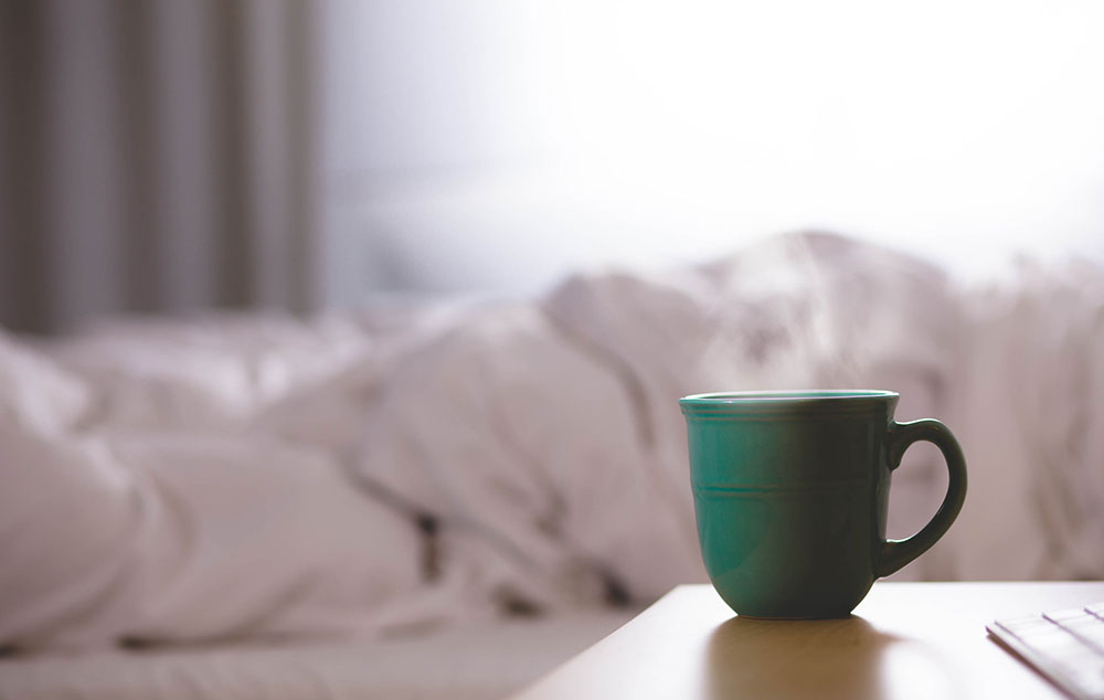 Green Coffee Cup On Bedside Table