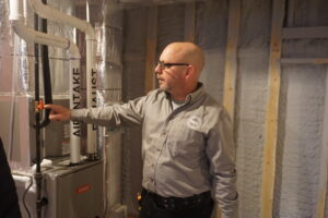 Home Inspector inspecting a forced-air furnace