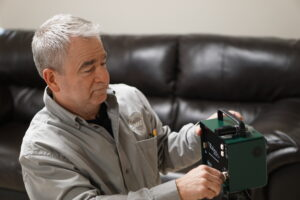 Inspector setting up a Continuous Radon Monitor