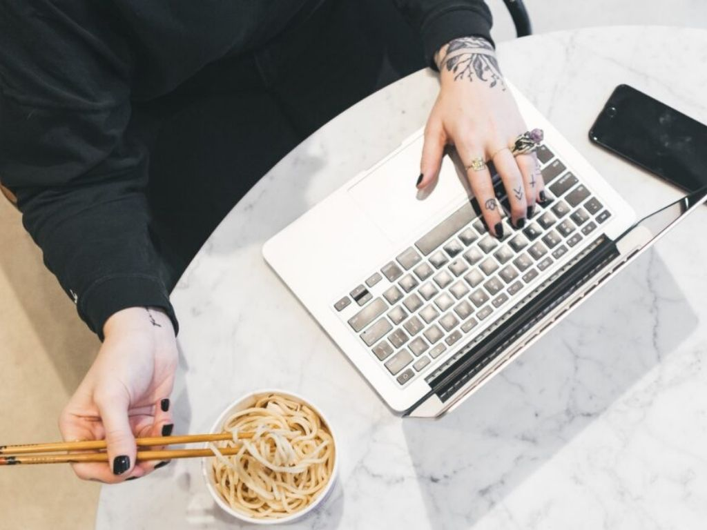 Woman eating noodles working on laptop