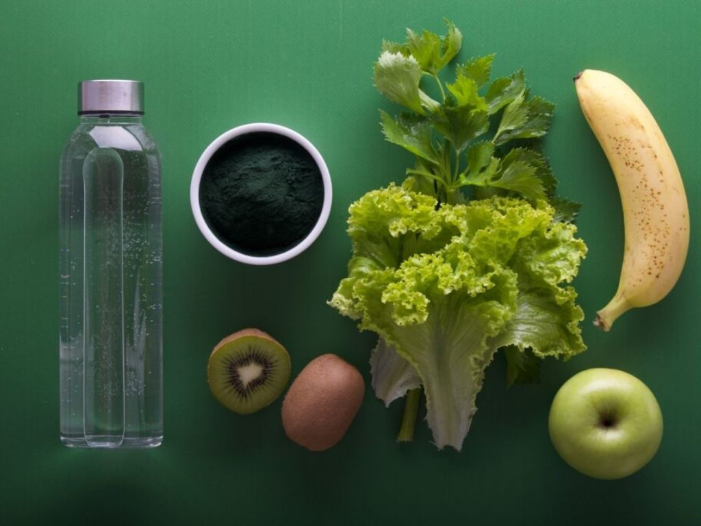Water Bottle, Lettuce, Banana, Apple and Kiwi on green background
